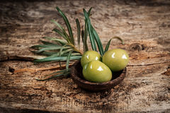 Olives with leaves. On a wooden surface Royalty Free Stock Photo