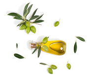 Olives with leaves and olive oil, above view. Top view of branch with green olives and a bottle of olive oil isolated on white background Stock Images