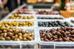 Olives on the marketplace. Assortment of olives on the marketplace. Rows of different types of olives in transparent plastic bowls stock image