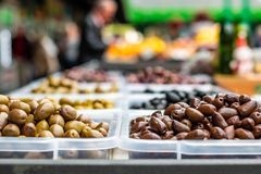 Olives on the marketplace. Assortment of olives on the marketplace. Rows of different types of olives in transparent plastic bowls. Blurred customers on royalty free stock image