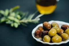 Olives naturelles, huile et branche verte sur le fond noir Images stock