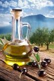 Olives noires avec la bouteille de pétrole sur une table en bois. Image stock