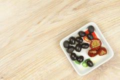 Olives noires et poivrons de cerise rouges bourrés du thon, sur la cuvette de porcelaine Photos libres de droits