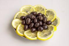 Olives noires et segments d'un citron Images stock