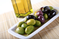 Olives and oil. Mixed olives in oil on a plate Royalty Free Stock Image