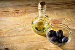Olives and oil bottle. Bottle of aromatic olive oil and some olives, the topic Healthy Eating Stock Image