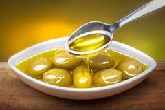 Olives in oil. Closeup photo of olives in olive oil on boat shaped  plate.oil is beeing poured on olives with spoon Stock Images