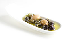 Olives, oil and spice on white plate Royalty Free Stock Photography