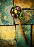 Olives in an old wooden ladle Stock Photo