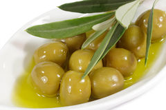 Olives in olive oil. Green olives in olive oil with branch on a plate Royalty Free Stock Images