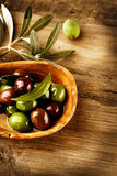 Olives and Olive Oil. Over wooden baackground Stock Photos