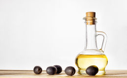 Olives and olive oil bottle. Bottle of aromatic olive oil and some olives, the topic Healthy Eating Stock Image