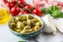 Olives olive oil mozzarella cheese tomatoes prosciutto basil leaves - ingredients italian or mediterranean cuisine Stock Photo