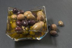 Olives with olive oil. On a shale stone Stock Photos