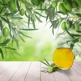 Olives and olive oil on white wooden board and abstract bokeh. Green food background Stock Photos