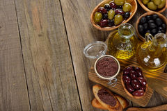 Olives and olive oil. On a wooden background Stock Photos