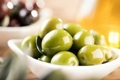 Olives and Olive Oil on wooden background in backlight stock image