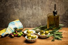 Olives and olive oil. On a wooden table Royalty Free Stock Photography