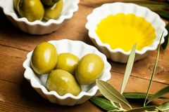 Olives and olive oil. On a wooden table Royalty Free Stock Image