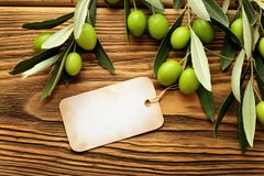Olive oil label. Olives over wooden background and olive oil label Stock Photos