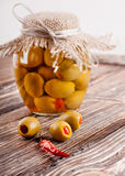 Olives with pepper. Bank of olives with pepper on a wooden board Royalty Free Stock Photo