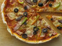 Italian Pizza Closeup delicious Slice. Olives, pepper, ham, cheese and tomato sauce Italian pizza in a wooden table royalty free stock images