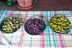 Olives and peppers. Traditional made olives and peppers on a village table Royalty Free Stock Images