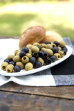 Olives On A Plate. On A Old Wooden Table With Green Grass In The Background Stock Image