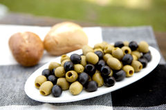 Olives On A Plate. On A Old Wooden Table With Green Grass In The Background Royalty Free Stock Photo
