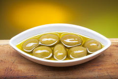 Olives on plate in oil. Closeup photo of olives on boat shaped plate in olive oil Royalty Free Stock Photography