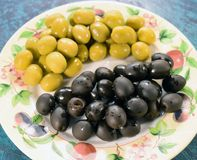 Olives in a plate. Tasty green and black Royalty Free Stock Photography