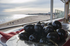 Olives platter overlooking the beach Royalty Free Stock Photography