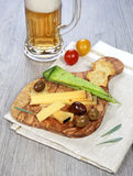 Olives provencal, solid cheeses and a glass of unfiltered beer Stock Photos