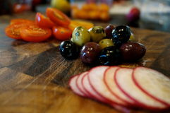 Olives and radish. Food on wood board Royalty Free Stock Photos