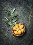 Olives in rustic bowl with oil and olive branch on dark vintage background Royalty Free Stock Photography