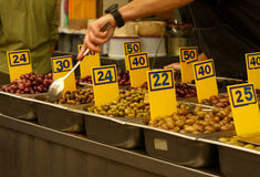 Olives for sale. In metal containers with numbered signs Stock Photos
