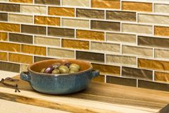 Olives in serving dish and wooden cutting board on engineered stone counter top with glass mosaic tile back splash in home kitchen