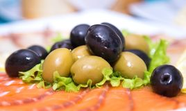 Olives and sliced salmon. Appetizer on italian restaurant. Royalty Free Stock Photo