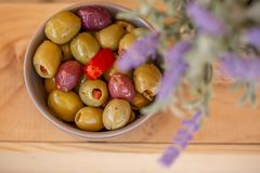 Olives in a small bowl on a wooden table. Lavender. Blurry background. Closeup. stock photos