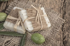 Olives and soap bars on wooden table. Natural olive oil soap bars and olives on wooden surface Royalty Free Stock Image