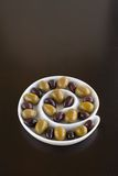 Olives in spiral dish. Green and Black olives in a sprial bowl Stock Photography