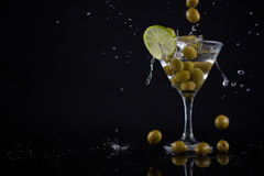 Olives splashing in to a cocktail martini with lime on table Stock Images
