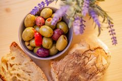Olives stuffed, red pepper and homemade bread. Multicolored olives in a small bowl on a wooden table. royalty free stock photography