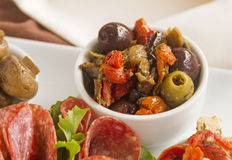 Olives And Sundried Tomatoes. Delicious black olives and stuffed green olives with sundried tomato Royalty Free Stock Photos