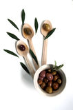 Olives. On three wooden spoons Stock Image