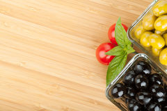 Olives, tomatoes and basil on cutting board Stock Photography