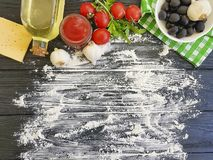 Olives, tomatoes, garlic, ketchup flour italian dinner vegetable preparing on a wooden background frame, cooking. Olives, tomatoes, garlic, ketchup flour on a stock images