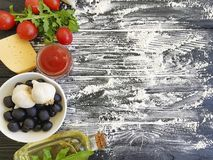 Olives, tomatoes, garlic, ketchup flour italian vegetable preparing on a wooden background frame, cooking. Olives, tomatoes, garlic, ketchup flour on a wooden stock photos