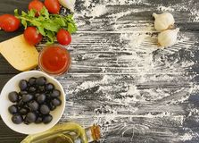 Olives, tomatoes, garlic, ketchup flour vegetable preparing on a wooden background frame, cooking. Olives, tomatoes, garlic, ketchup flour on a wooden background stock images