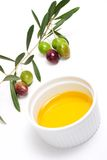 Olives twig and pure olive oil. Extra-virgin olive oil and green olives branch on white background Royalty Free Stock Image